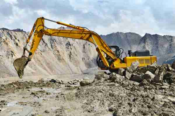large yellow excavator in granite quarry